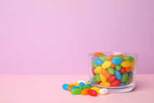 Glass Of Delicious Jelly Beans On Color Background. Space For Text