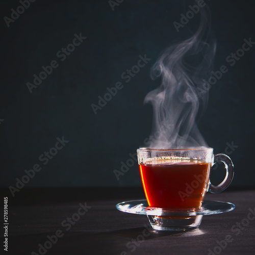 Autocollant pour porte The Freshly brewed black tea in a transparent glass Cup,escaping steam