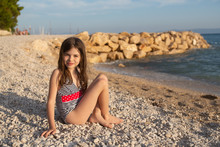 Young Beautiful Girl With Wet Hair In A Swimsuit Posing On The Beach Of The Adriatic Sea
