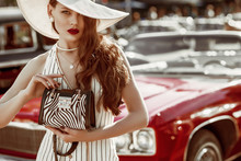 Outdoor Fashion Portrait Of Young Elegant Luxury Lady Wearing Wide Brim Hat, Striped Linen Jumpsuit, Pearl Earrings, Necklace, Holding Animal Print Bag, Posing Near Red Retro Car. Copy, Empty Space