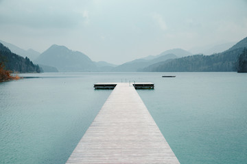 Fototapeta Minimalistyczny Scenic panorama view of an idyllic wooden landing stage on a beautiful lake in the Alps on a moody cloudy day in summer with retro vintage filter effect