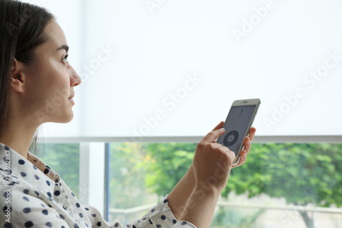 Tablou Canvas Woman using smart home application on phone to control window blinds indoors