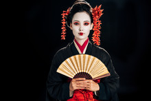 Geisha In Black Kimono With Red Flowers In Hair Holding Traditional Asian Hand Fan Isolated On Black