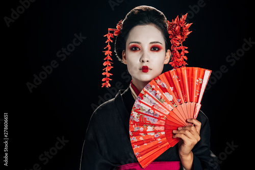 attractive geisha in black kimono with flowers in hair holding bright hand fan isolated on black with copy space