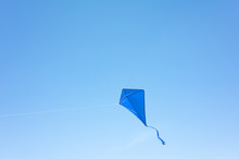 A Blue Kite Soars In A Cloudless Sky. The Concept Of Freedom, Summer Hobbies, Entertainment In Nature. Minimalism, Space For Text, Shades Of Blue.