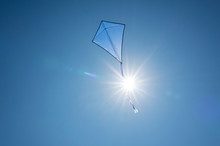 A Blue Kite Soars In A Cloudless Sky With A Bright Summer Sun With Beautiful Rays. The Concept Of Freedom, Summer Hobbies, Entertainment In Nature. Minimalism, Space For Text, Shades Of Blue.
