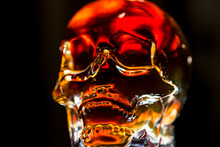 Glass Skull With Backlight. Glass Skull Glowing With Golden Light On A Dark Background