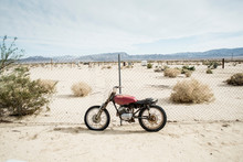An Old Motorbike Leans Against Broken Fence In The Desert, Joshua Tree