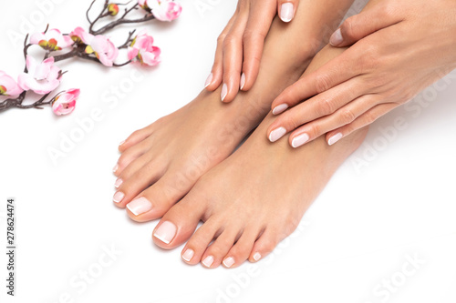Poster Manicure Female feet and hands with nice pedicure and manicure isolated on white background.
