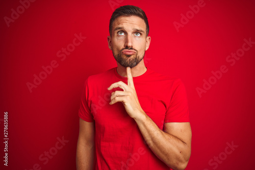 Canvastavla Young handsome man wearing casual t-shirt over red isolated background Thinking