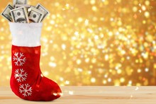 Lot Of Dollars In A Christmas Sock On Background