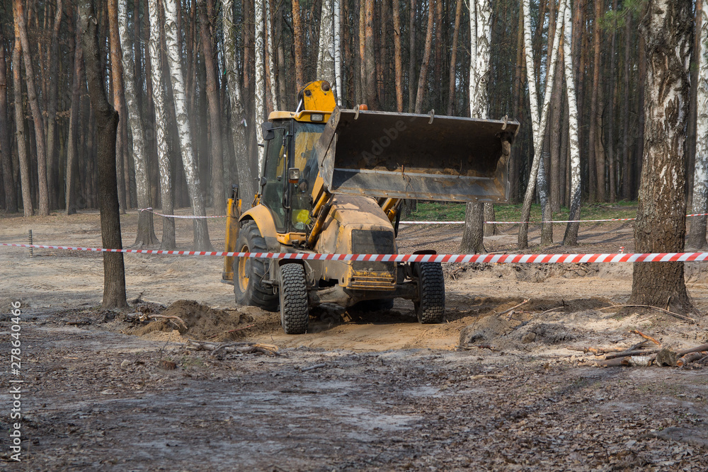 Fototapeta Tractor digs the ground in the forest area. Industrialism