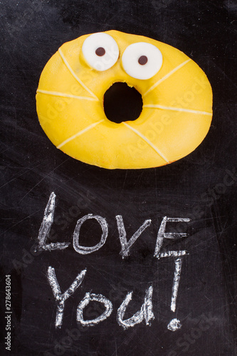 Funny yellow donut and inscription I love you. Surprised donut on black background. Idea for Valentines holiday.