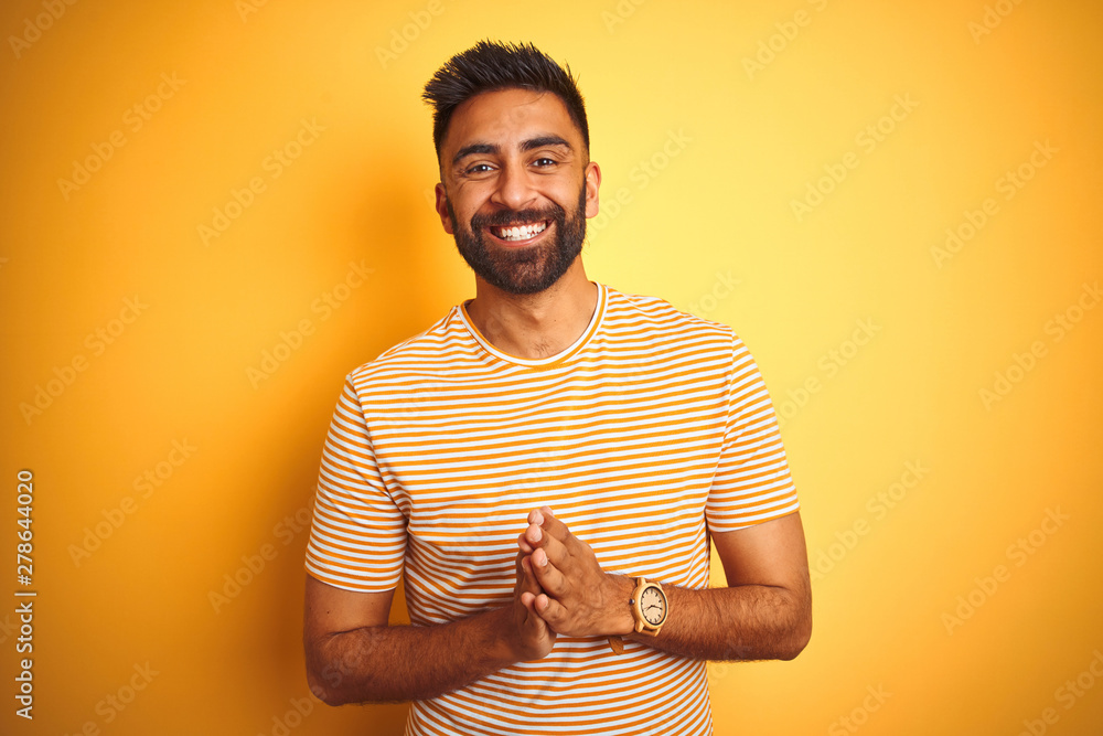 Fototapety, obrazy: Young indian man wearing t-shirt standing over isolated yellow background Hands together and fingers crossed smiling relaxed and cheerful. Success and optimistic