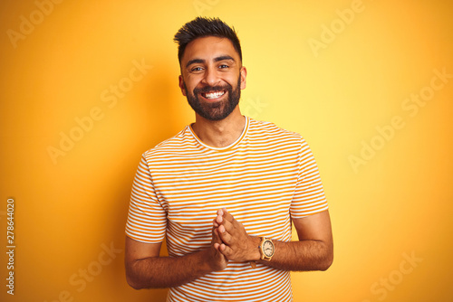 Young indian man wearing t-shirt standing over isolated yellow background Hands together and fingers crossed smiling relaxed and cheerful. Success and optimistic - 278644020