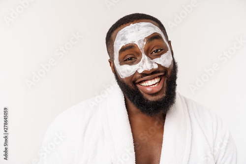 Türaufkleber Spa Young african-american guy applying face cream on white background. Portrait of a young happy smiling african man at studio. High fashion male model.