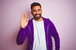 Young indian man wearing purple sweatshirt standing over isolated pink background Waiving saying hello happy and smiling, friendly welcome gesture
