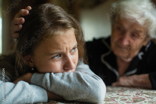 Fotografía Teen girl cries, grandmother soothes and strokes her head.