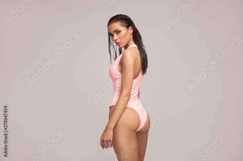 Sexy woman in pink swimwear posing.