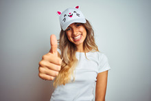 Young Beautiful Woman Wearing Cat Cap Over Grey Isolated Background Happy With Big Smile Doing Ok Sign, Thumb Up With Fingers, Excellent Sign