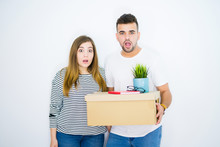 Young Couple Holding Cardboard Box Moving To A New Home Over White Isolated Background Scared In Shock With A Surprise Face, Afraid And Excited With Fear Expression