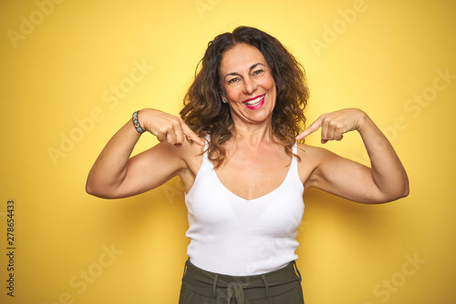 Fotografie, Obraz  Middle age senior woman with curly hair standing over yellow isolated background looking confident with smile on face, pointing oneself with fingers proud and happy