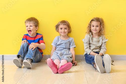 Fotografía  Cute little children sitting near color wall