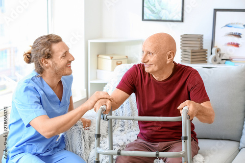 Obraz Elderly man with caregiver in nursing home - fototapety do salonu