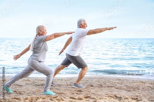 Pinturas sobre lienzo  Mature couple practicing yoga at sea resort