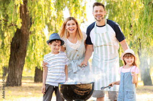 Fotografía Happy family cooking tasty food on barbecue grill outdoors