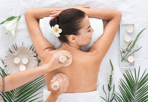 Foto Beautiful young woman receiving massage in spa salon