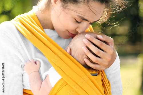 Obraz Young mother with her baby in sling walking in park - fototapety do salonu