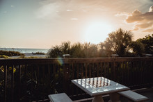 Recreation And A Beachside Chess Board Sits Empty In Front Of A Beautful Golden Tropical Sunset On The Beach