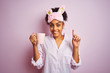 Afro woman wearing pajama and mask drinking a cup of coffee over isolated pink background surprised with an idea or question pointing finger with happy face, number one