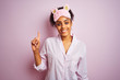 Young african american woman wearing pajama and mask over isolated pink background showing and pointing up with finger number one while smiling confident and happy.