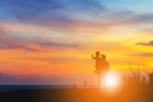 Silhouette Of Grandfather And Grandchild Looking Sun Down And Walking On The Beach Evening Sunset Background, Happy Family Concept