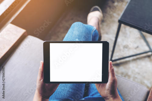 Top view mockup image of a woman holding black tablet pc with blank white screen while sitting in cafe
