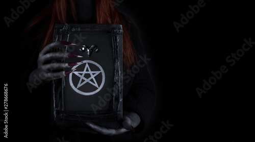 Hands of a witch with long claws holding a spell magic book with pentagram symbol on it Tapéta, Fotótapéta