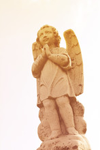 Beautiful Angelic Winged Cherub. Close Up Of Garden Cherub Angel Statue With Wings Carved From Granite Stone, Religious Symbol Brining Hope And Love.