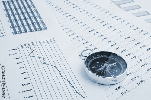 Fotografía  Navigation in financial world, compass on financial charts and graphs