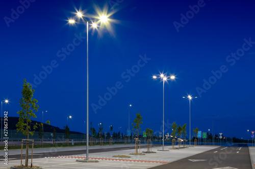 big modern empty parking lot with modern bright LED street lights at night