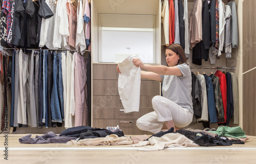 Cuadros en Lienzo Young woman throwing clothes in walk in closet