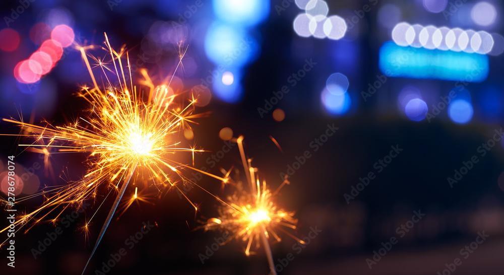 Fototapety, obrazy: Sparkler with blurred street light background