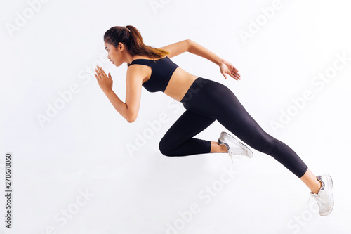 Fototapeta Side view of slim Asian female in black sportswear sprinting fast during workout
