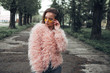 Leinwanddruck Bild Portrait of One Stylish Girl in Pink Coat and Modern Yellow Sunglasses Posing on Street