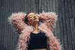 Leinwanddruck Bild Close Up Portrait of One Stylish Girl in Pink Coat and Modern Yellow Sunglasses Posing on Street