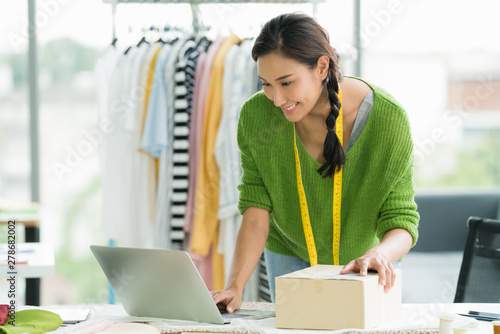 Foto  Young Asian woman entrepreneur / fashion designer working in studio and packing