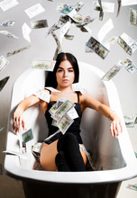 Sexy Female And Dollar Bills. Woman With Lot Of Money. Millionaire Woman Lying In Bedroom. Sexy Woman Lying In Dollar Bills. Rich Sexy Woman Lies On Money. Currency, Women, Winning.