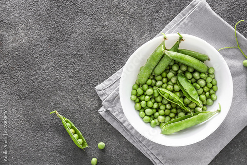 Stampa su Tela Bowl with tasty fresh peas on dark background