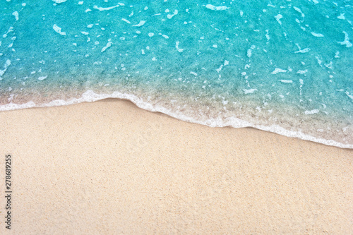 Soft blue ocean wave on clean sandy beach